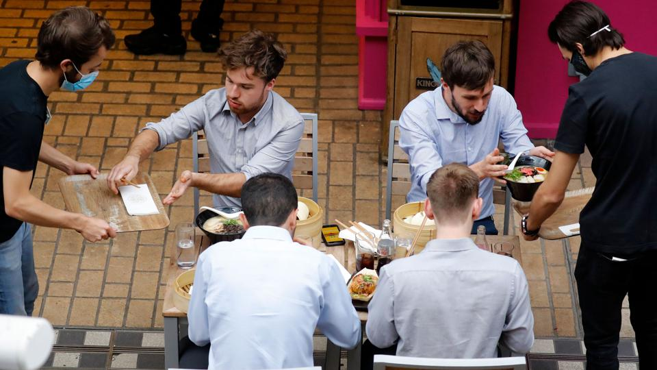 People being served food at an outdoor table.