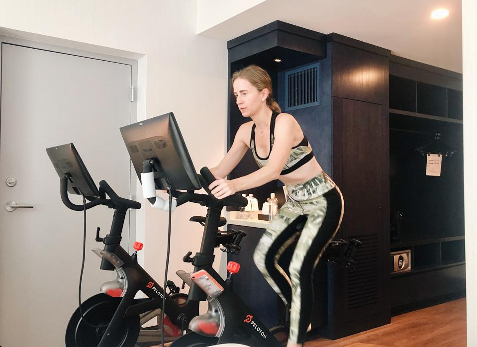 A woman on a stationary bike in a hotel.