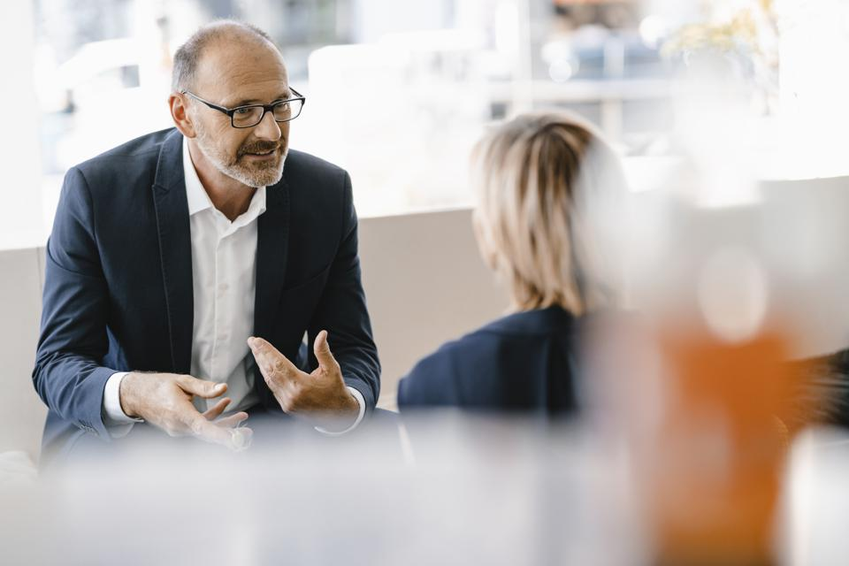 Businessman and woman having a meeting in a coffee shop, discussing work