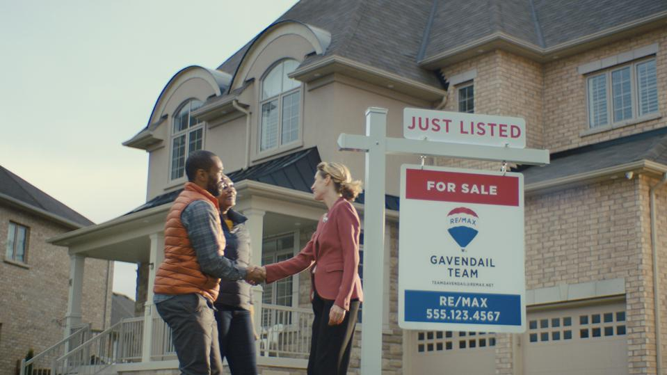 Real Estate agent shaking hands with new home owners.