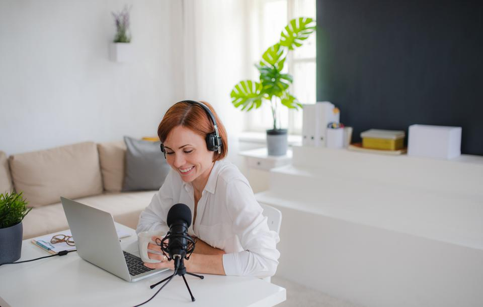 Woman vlogger or blogger with laptop and headphones, talking.