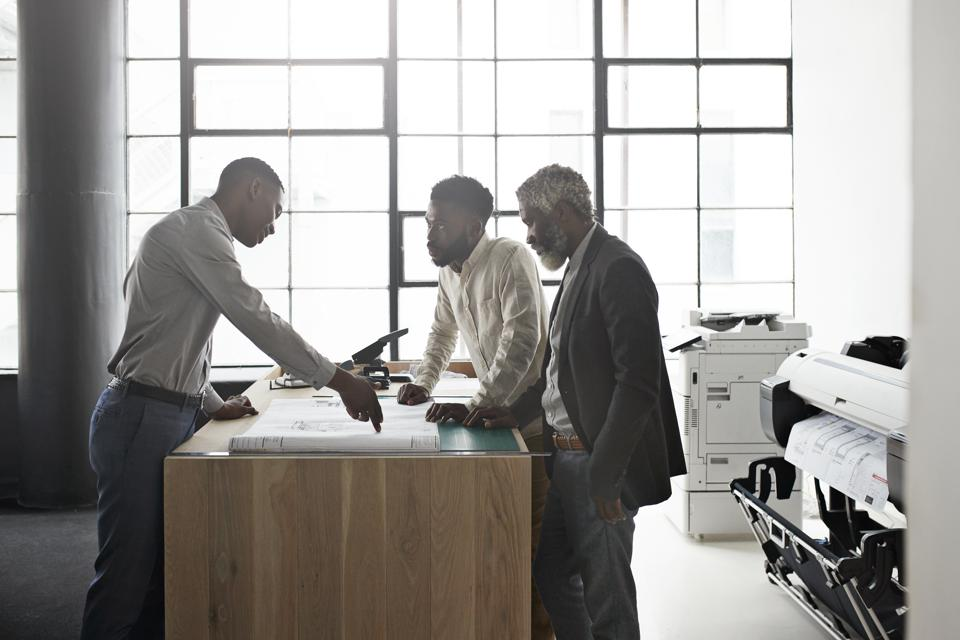 Entrepreneur and coworkers discussing at workplace