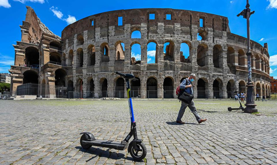 Man wearing mask walks past the Colosseum in Rome Italy amid coronavirus travel ban