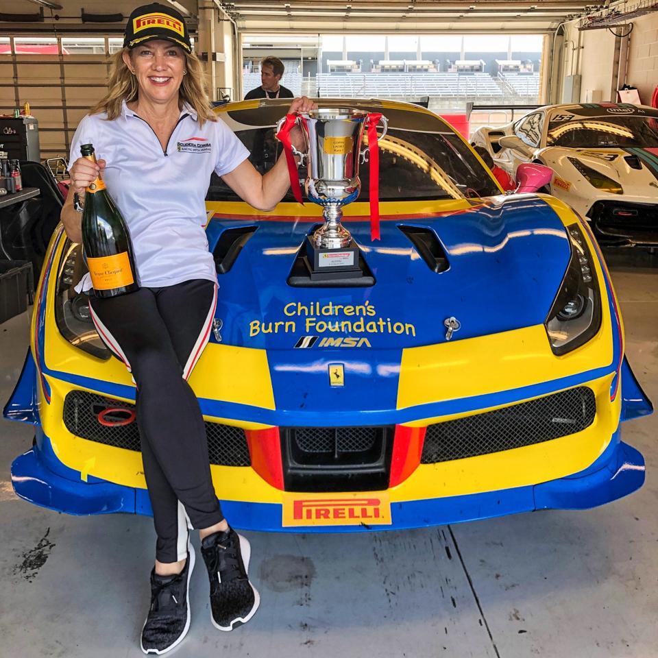 Lisa Clark sitting on her Ferrari Challenge race car
