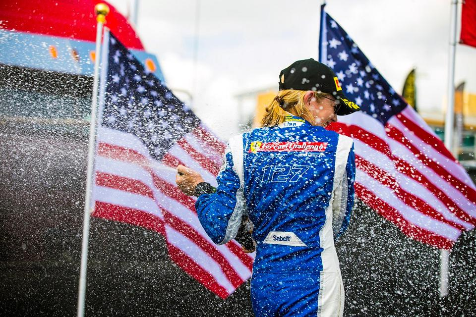 Lisa Clark spraying champagne on the podium