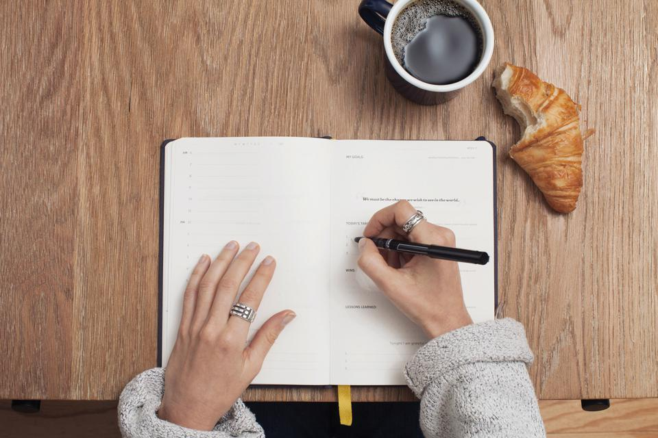 Woman writing in planner with coffee on the table