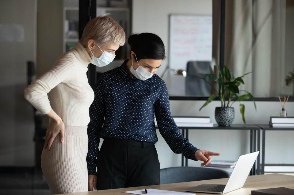 Focused women wearing masks in office.