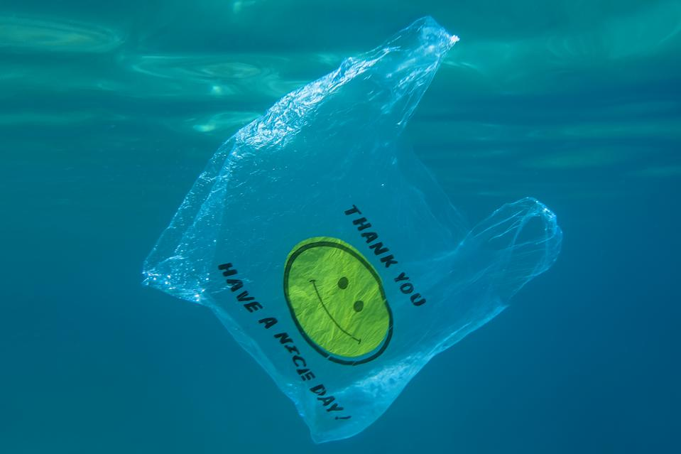 Plastic bag with a yellow smiley face and the words ″Thank you -Have a nice day!″ slowly drifts underwater in the blue water. Becici, Budva Municipality, Montenegro, Europe