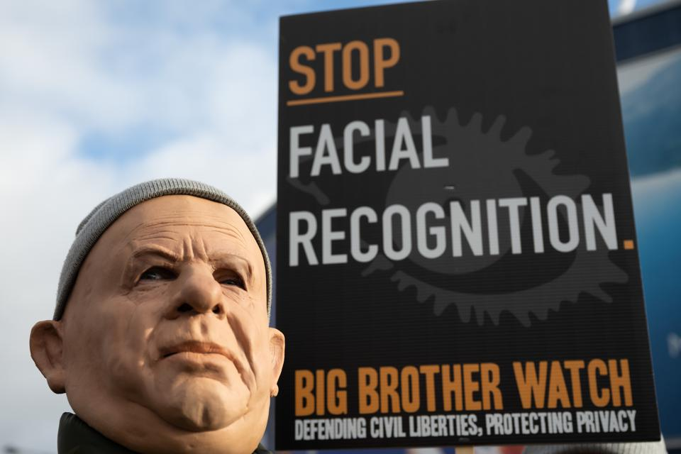 Man in mask holding a placard protesting against the use of facial recognition technology