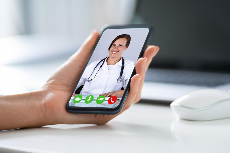 Businessperson Videochatting With Doctor On Smartphone