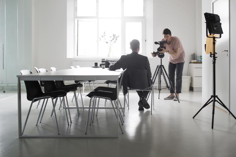 Photographer recording interview of businessman in board room