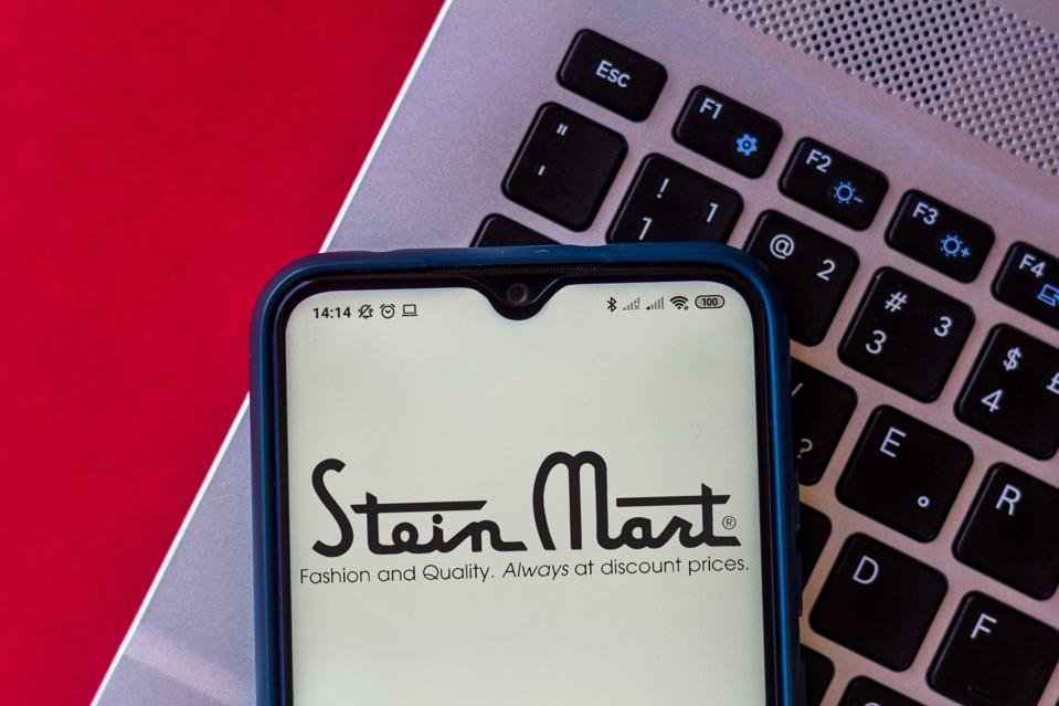 In this photo illustration, a Stein Mart logo seen displayed next to a computer