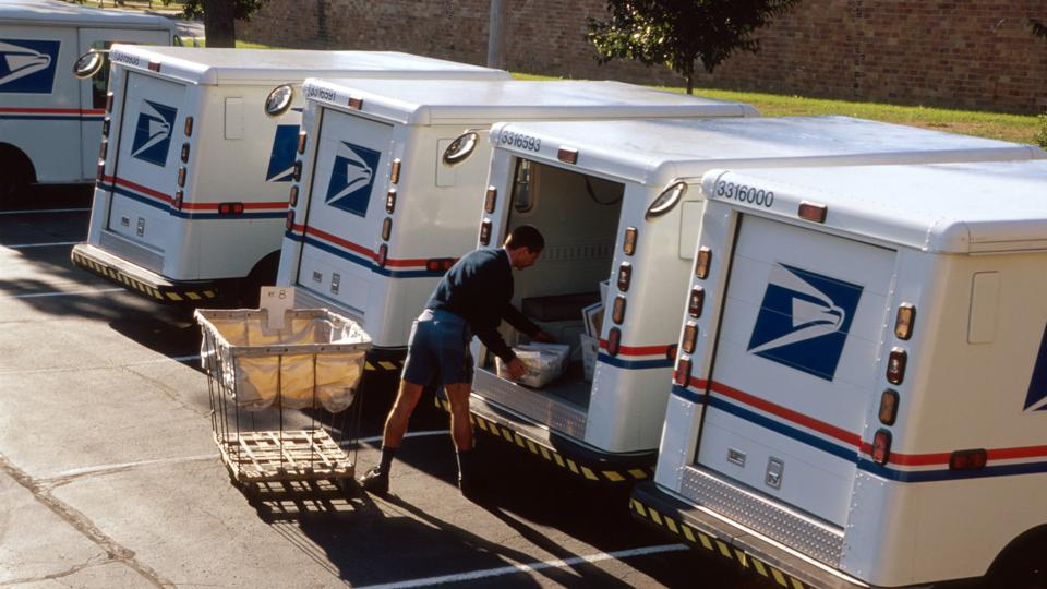 US Post Office, mail carrier loading truck