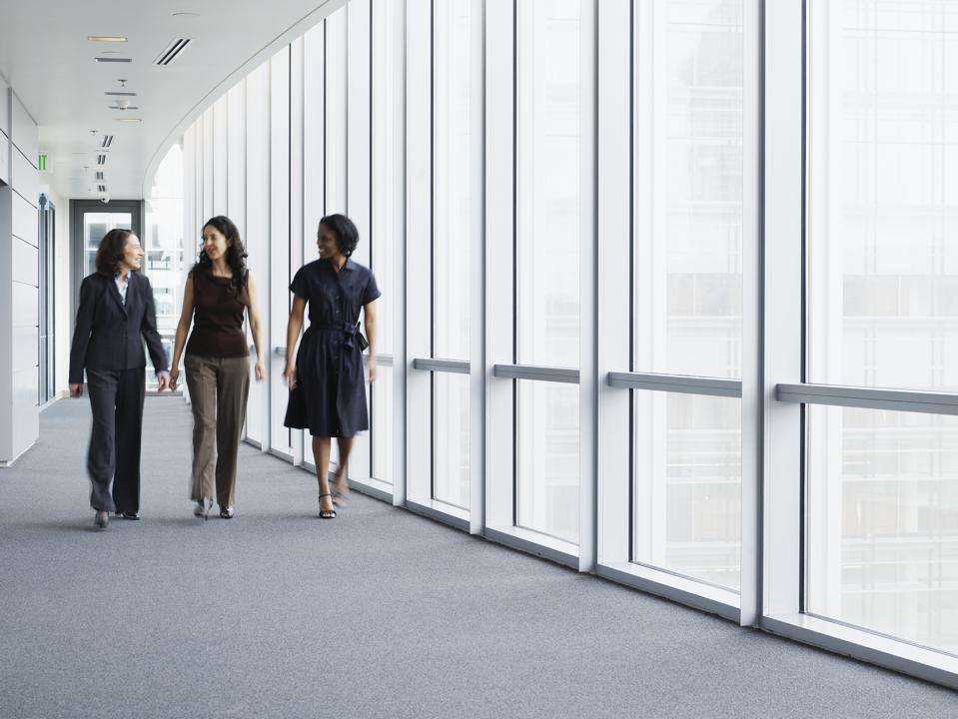 Businesswomen walking in hallway, smiling, portrait