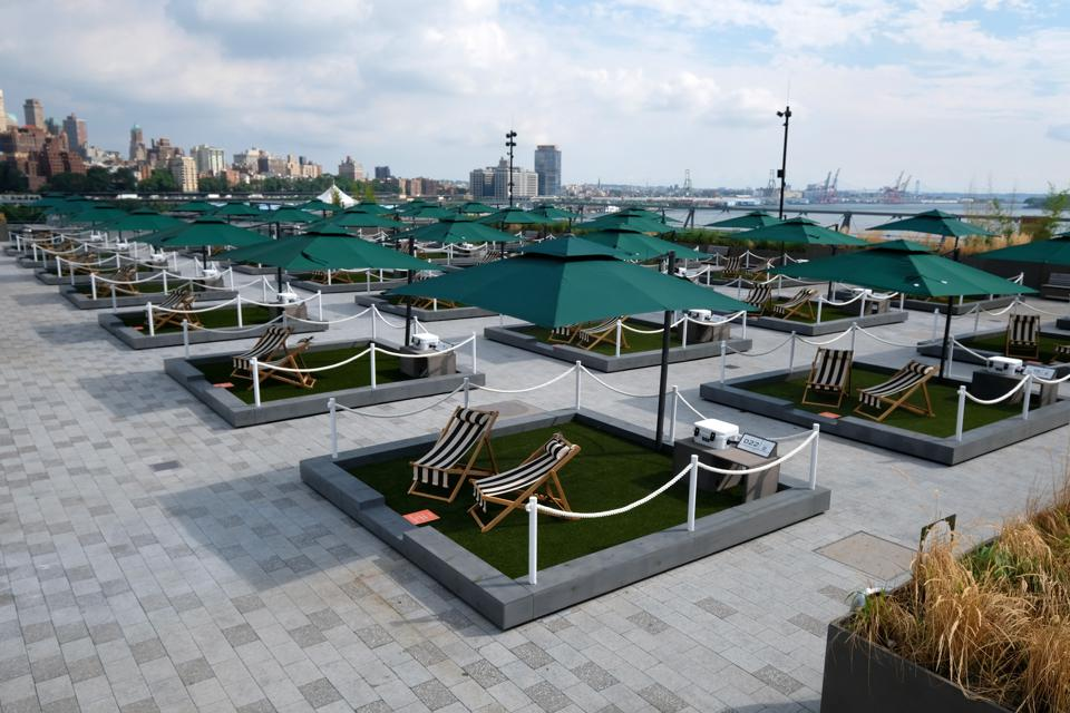 Blocks of mini lawns with umbrellas on the rooftop of Pier 17 overlooking the East River