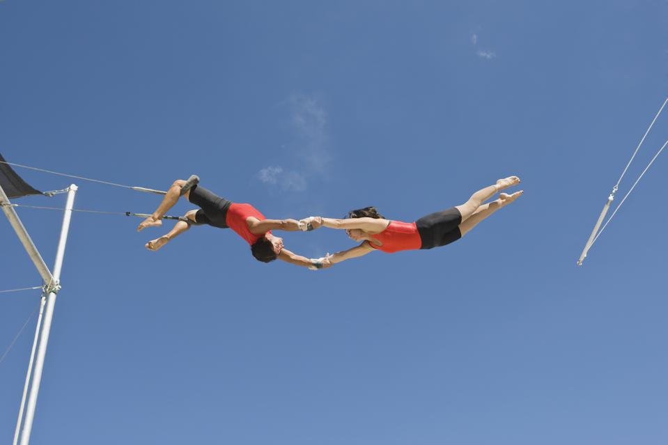 Male trapeze artist catching woman, low angle view
