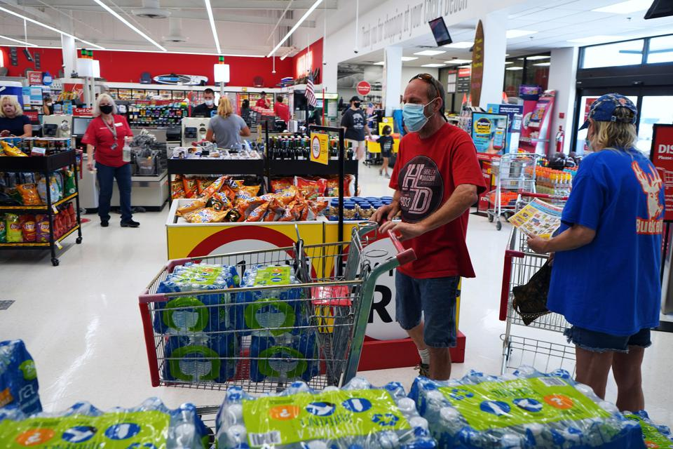 A shopper wearing a protective face mask fills a grocery...