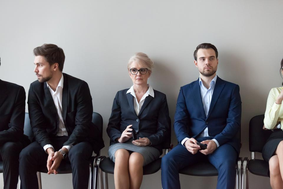 Young and mature candidates waiting for job interview in office