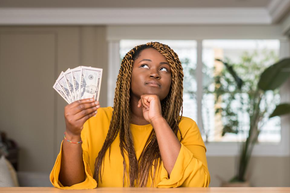 African american woman holding dollars serious face thinking about question, very confused idea