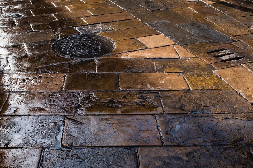 Wet old stone-paved flooring in Plaça del Pi (Pine Square), Barcelona, Spain.