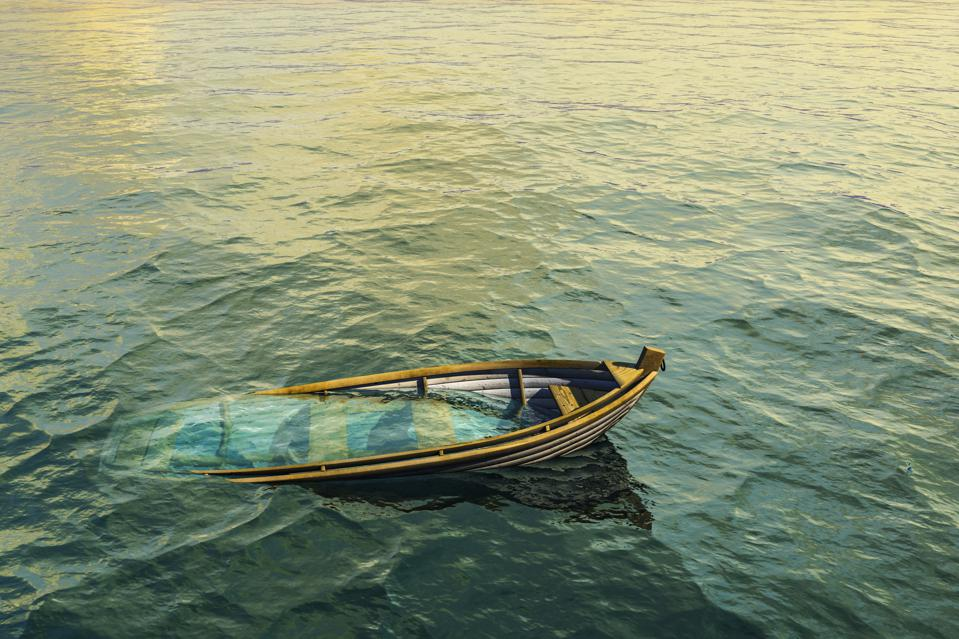 Abandoned sinking rowboat in ocean