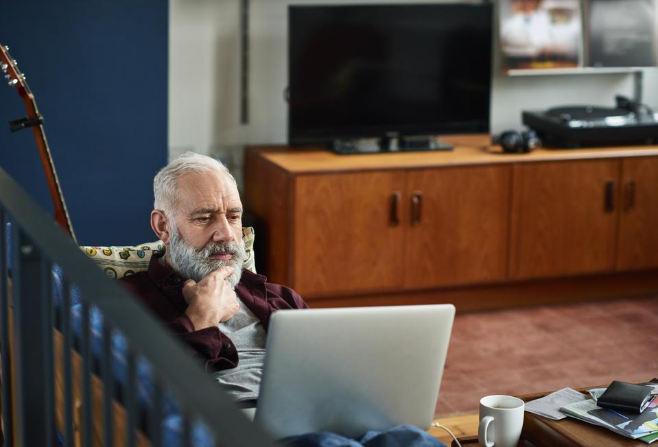 Pensive senior man using laptop with hand on chin