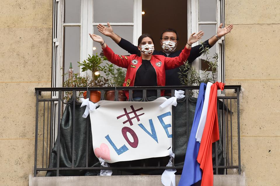 Couple reunite in Paris, France with a love sign on the balcony of their apartment