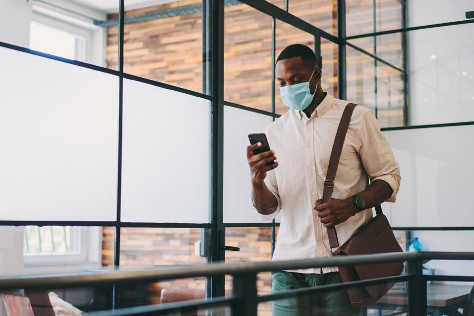 Black gent checks mobile while wearing a mask. (Weird to write that, but here we are.)