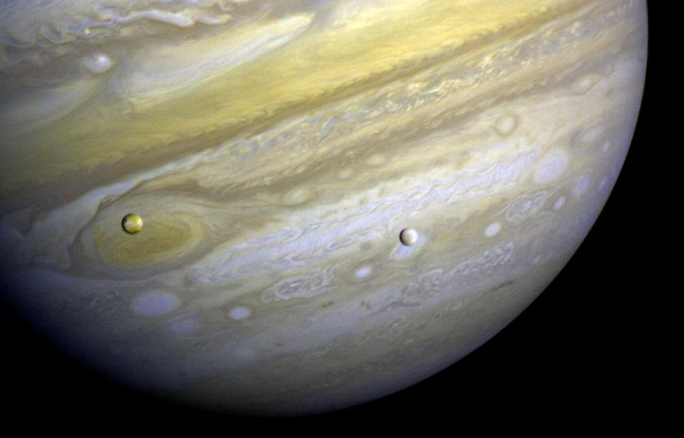 Voyager 1 took this photo of Jupiter and two of its satellites: Io and Europa.