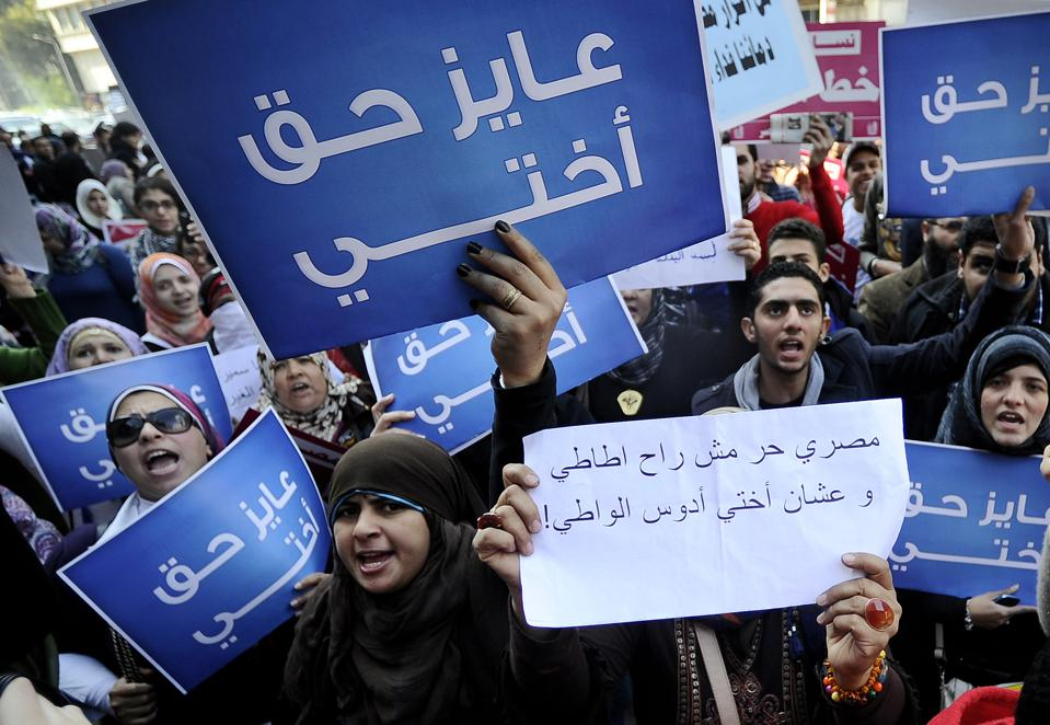 Egyptian women hold placards that read i
