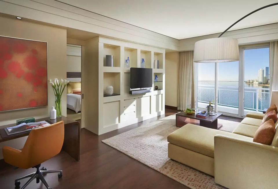 A contemporary hotel suite living room with a view of the bay out of the window.