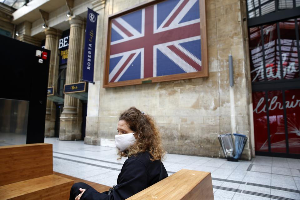 A passenger wearing a mask awaits her Eurostar train to UK from Paris near British flag