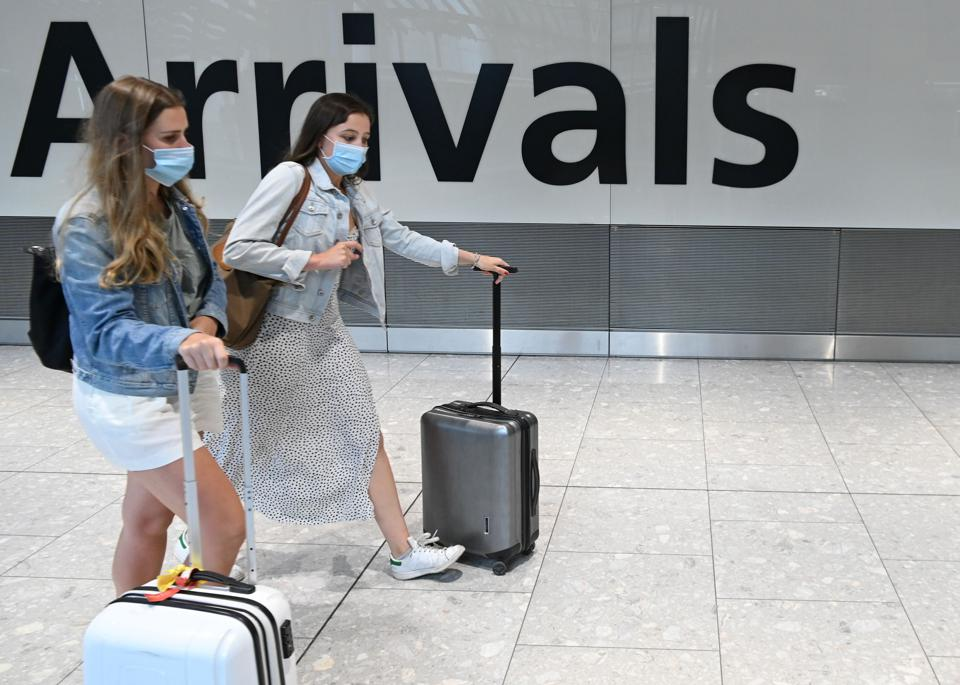 Passengers wearing Covid protective face masks arrive at Heathrow airport UK