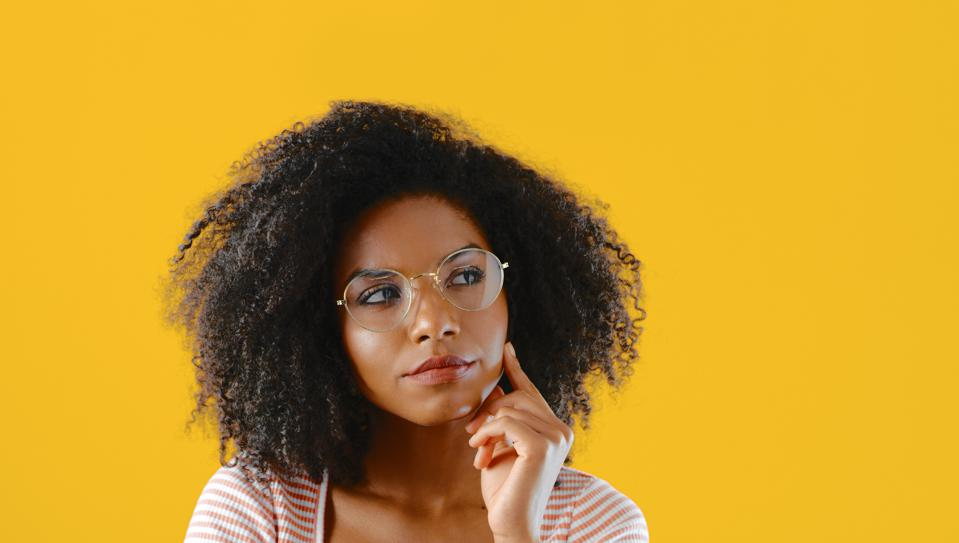 Cropped shot of a young woman looking thoughtful against a yellow background