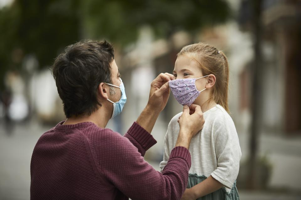 Father helping his daughter put on a face mask due to the COVID-19 pandemic.
