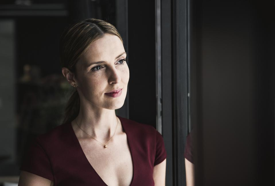 Portrait of woman looking out of window
