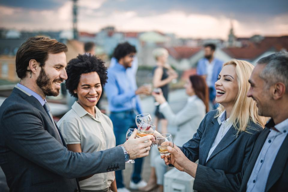 Cheerful business colleagues toasting with alcohol at the outdoor party.