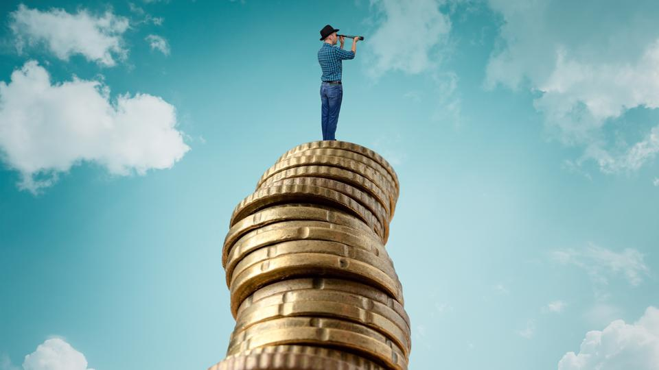 Man standing on stack of coins and looking at telescope