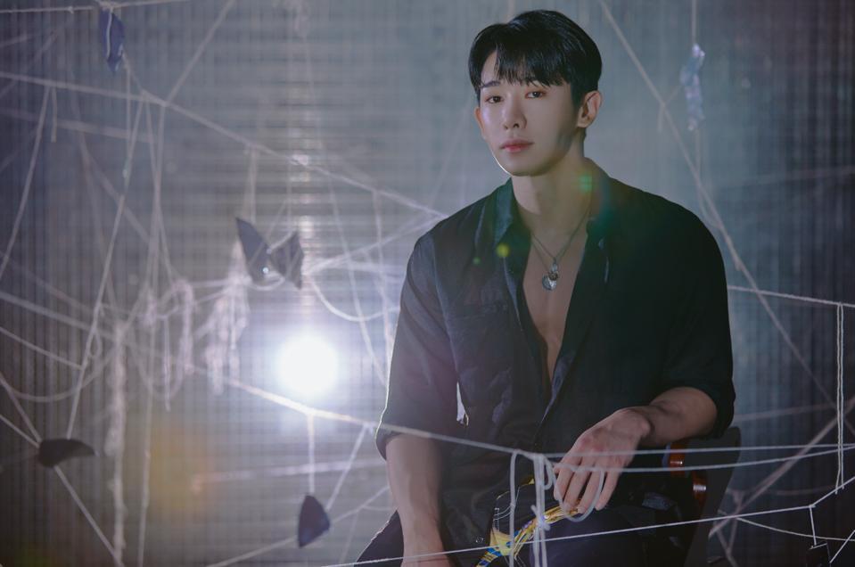 K-pop tar Wonho sitting amid strings in dark lighting, staring at the camera.