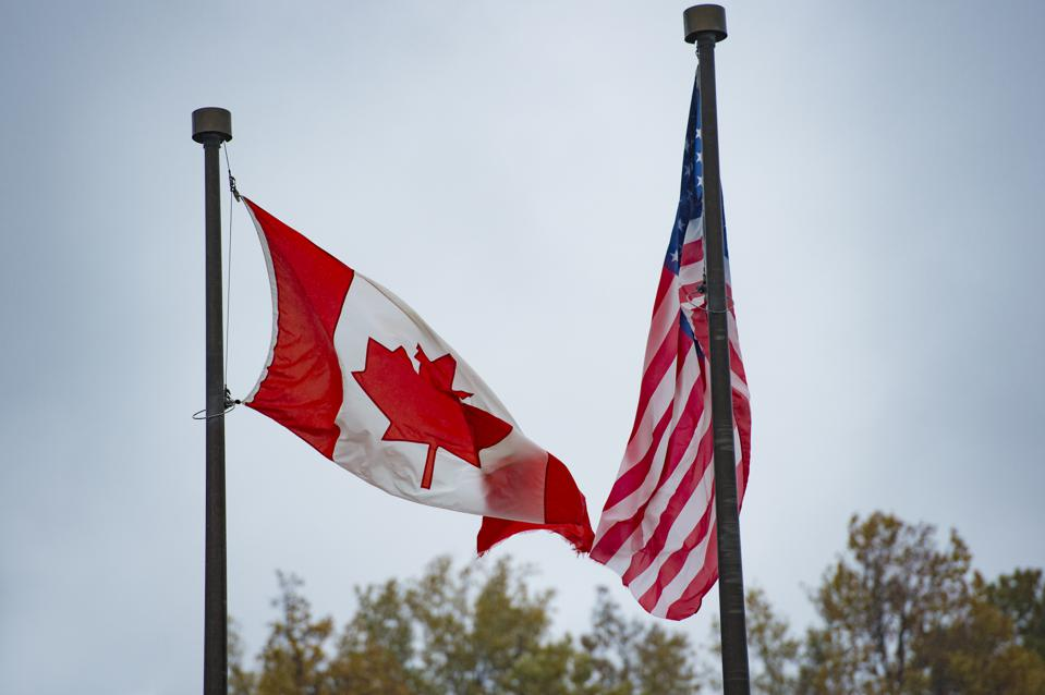 Close-up view of an American flag and a Canadian flag waving in the wind.