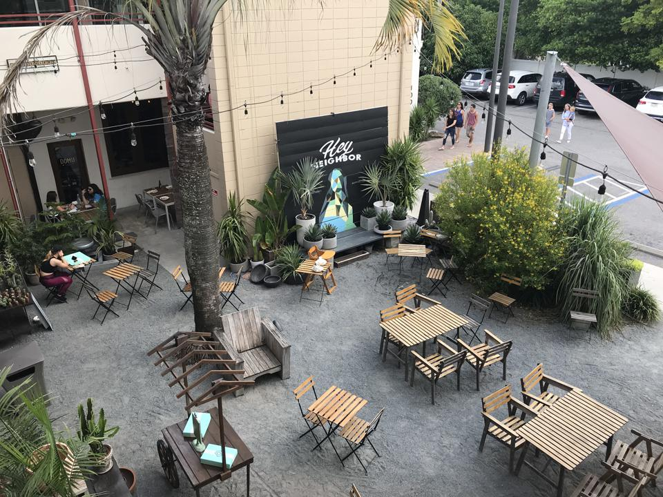 An outdoor restaurant terrace, viewed from above, at East End Market, with mostly empty tables and several trees.
