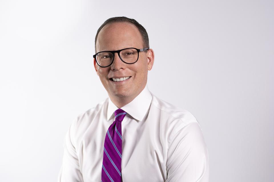Man wearing a white dress shirt, pink & purple tie.