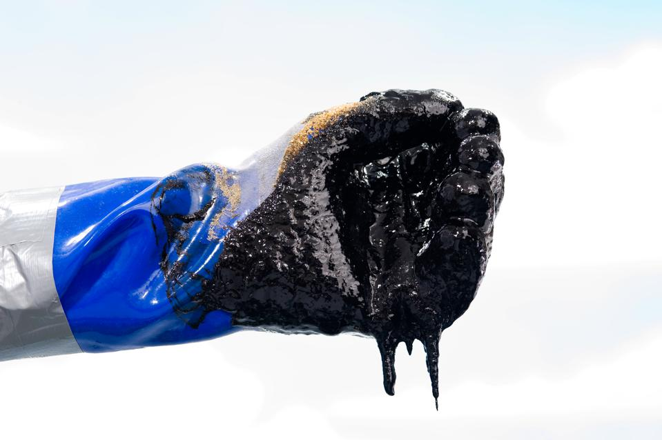 Oiled covered gloved hand during Oil spill clean up