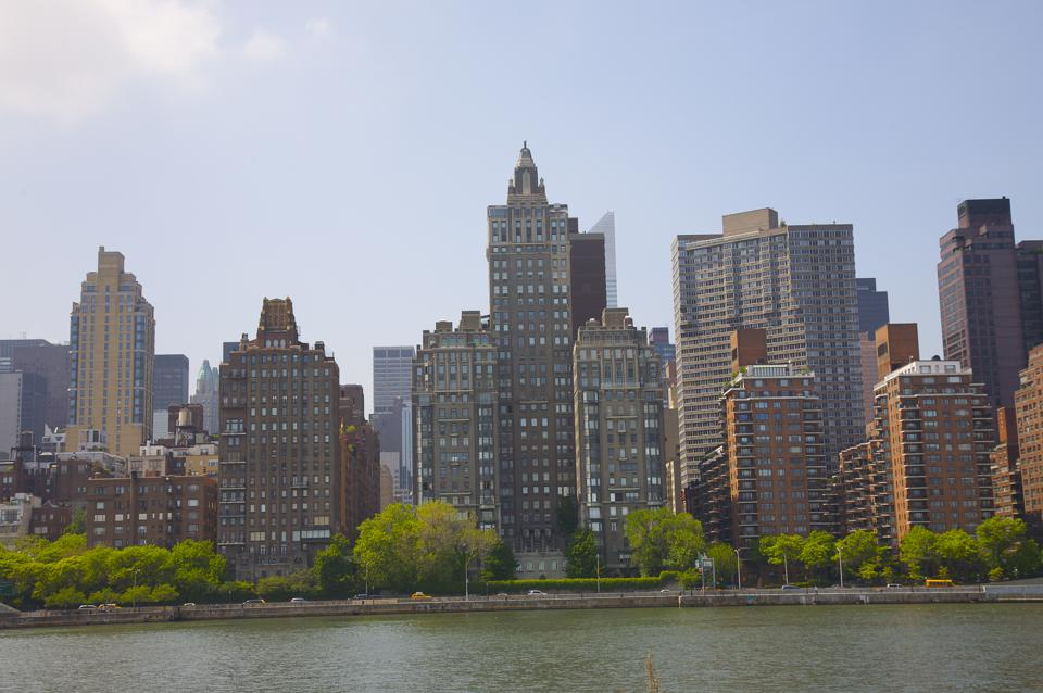 Luxury coops and condominiums on Manhattan's East Side, with parks, FDR Drive and East River, seen from southern tip of Roosevelt Island