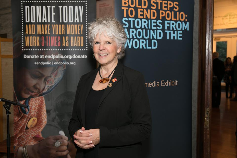 An older woman with white hair in black dress stands in front of End Polio panels