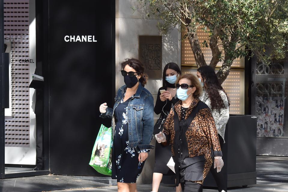 Women wearing face masks pass next a Chanel store on the Champs Elysées Paris France