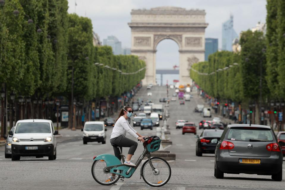 A cyclist wears a face mask as she crosses The Champs Elysées Avenue in Paris France