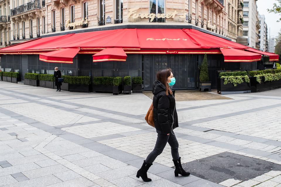 Woman wears face mask in Paris while walking down the Champs Elysées Avenue