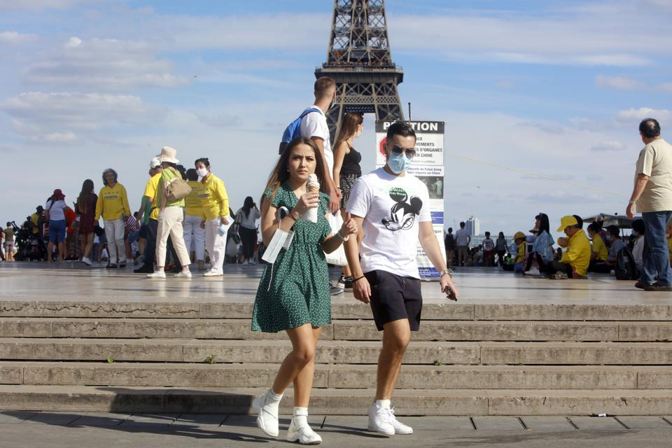 Tourists wearing a protective mask walk a front the Eiffel Tower in France.