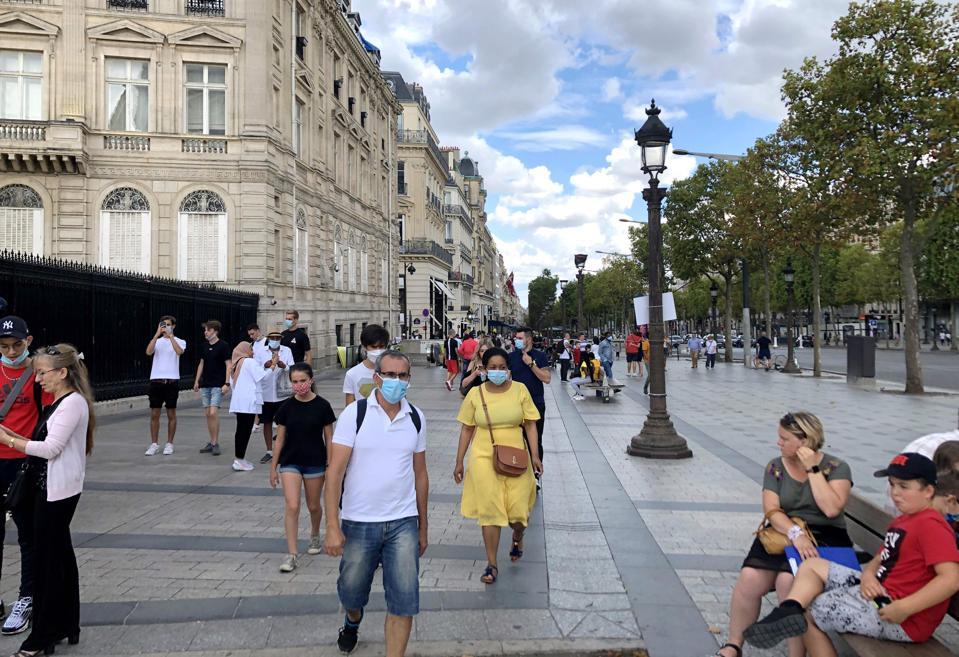 People wearing masks on the empty Champs-Elysées Paris France